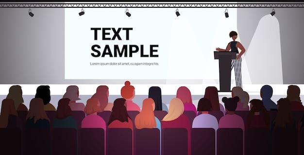 Afroamericana hablando a la audiencia desde la tribuna del club de mujeres niñas apoyándose mutuamente unión de feministas concepto sala de conferencias copia interior espacio vector illustrat