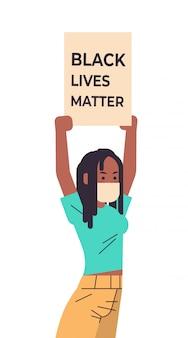 Afroamericana en máscara sosteniendo la bandera de la materia de vidas negras campaña contra la discriminación racial