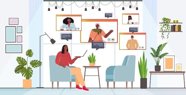 Afroamericana tener reunión virtual con miembros de la familia en las ventanas del navegador web durante la videollamada concepto de comunicación en línea salón horizontal interior