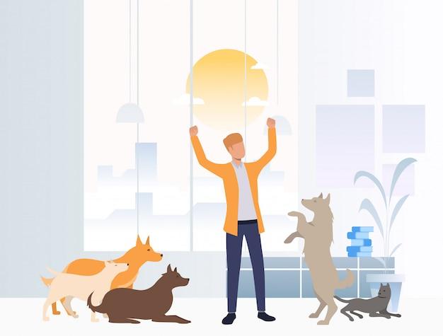 Alegre voluntario cuidando perros en refugio de animales