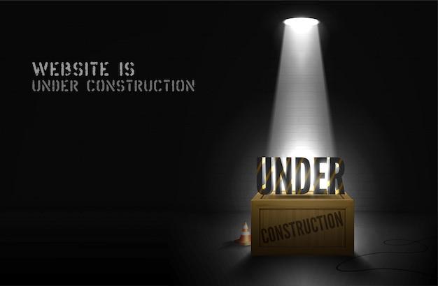 Alerta de construcción en caja de madera en focos sobre fondo negro. el sitio web estará disponible pronto con texto reflejado en la escena. banner oscuro de la página web con mensaje brillante