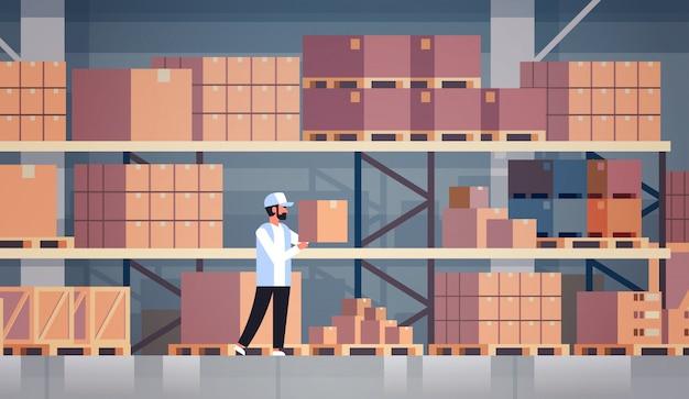 Almacenista trabajador de almacén pone caja de cartón en estante