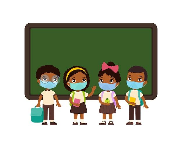 Alumnos con máscaras médicas en sus rostros. piel oscura niños y niñas vestidos con uniforme escolar de pie cerca de los personajes de dibujos animados de pizarra. protección contra virus, concepto de alergias.