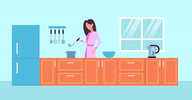 Ama de casa con cuchara mujer cocinar comida concepto moderno cocina interior horizontal retrato