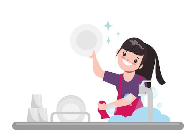Ama de casa está lavando el plato en la cocina.