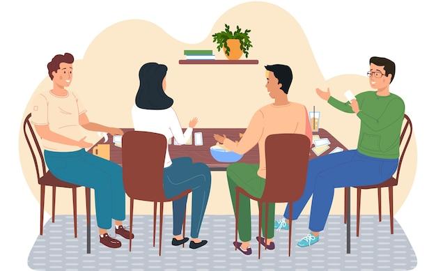Amigos jugando a las cartas sentados en una mesa, jóvenes pasando un buen rato juntos en casa o café. la gente feliz descansa, bebe bebidas con dulces y juega un juego de mesa. juegos familiares amistosos