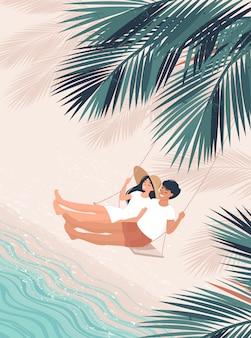 Amoroso hombre y mujer columpiarse en un banco bajo la palma de coco junto al mar