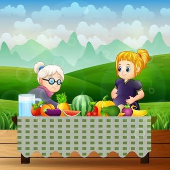 Anciana y una mujer embarazada con diferentes frutas.