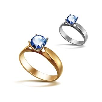 Anillos de compromiso de oro y plata con diamante transparente azul brillante de cerca aislado en blanco