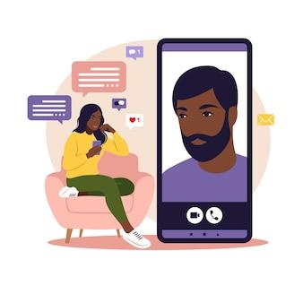 Aplicación de citas o concepto de chat la mujer africana está sentada con un gran teléfono inteligente en el sofá y hablando por teléfono