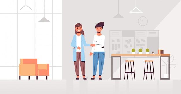 Apretón de manos de las empresarias socios comerciales apretón de manos durante el acuerdo de asociación compañeros de pie en el centro de trabajo creativo interior de la oficina moderna