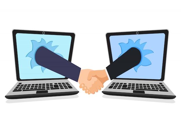 Apretón de manos a través de los dos monitores, computadoras portátiles.