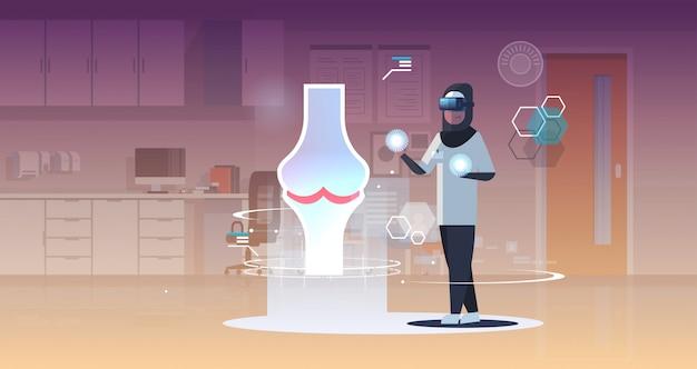 Árabe médico enfermera con gafas digitales mirando realidad virtual articulación de la rodilla órgano humano anatomía