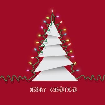 Árbol de navidad hecho de pedazos de papel y luces de guirnaldas