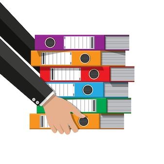 Archivos en mano, carpetas de anillas, carpetas de oficina coloridas. vista lateral. burocracia, trámites y despacho.