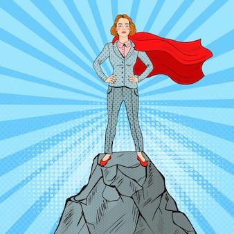 Arte pop confidente mujer de negocios superhéroe en traje con capa roja de pie en el pico de la montaña.