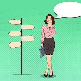 Arte pop doubtfull mujer de negocios en signo de puntero de cruce de caminos.