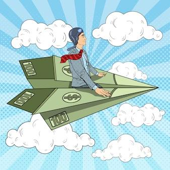 Arte pop exitoso hombre de negocios volando en avión de papel dólar.