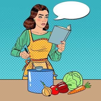Arte pop hermosa ama de casa cocinando sopa en la cocina con libro de recetas. ilustración