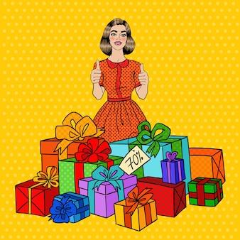 Arte pop hermosa mujer con enormes cajas de regalo y pulgares arriba.