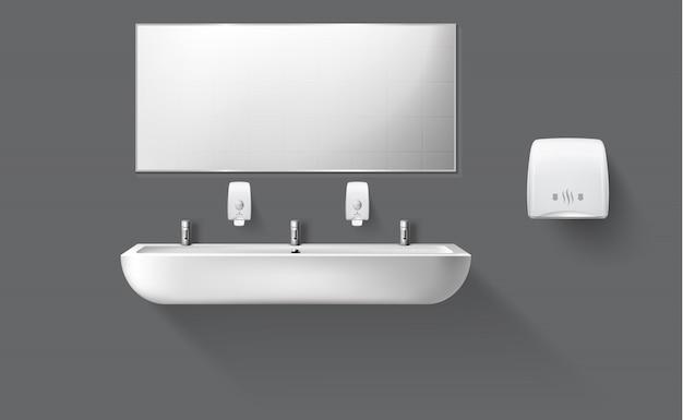 Aseo público con lavabo de cerámica y espejo.