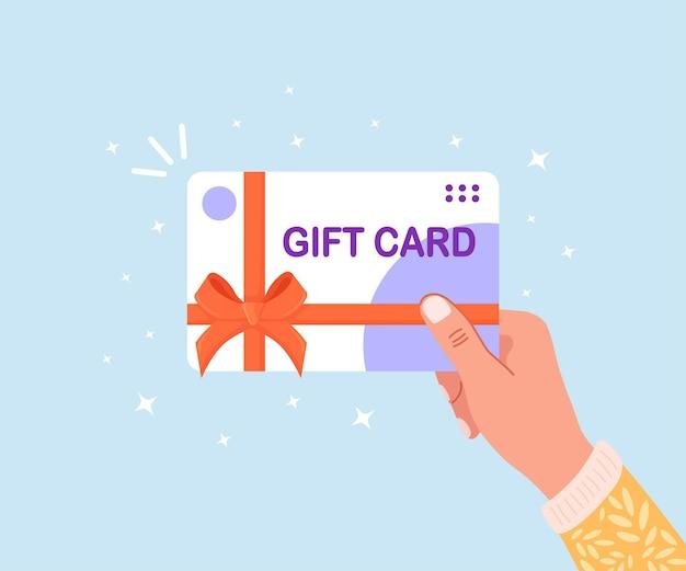 Asimiento de la mano humana tarjeta de regalo, vale o cupón. certificado de descuento comercial para clientes