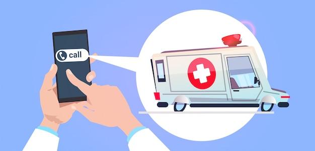 Asimiento de la mano llamadas de teléfono inteligente en el servicio de emergencia con ambulancia coche en chat bubble