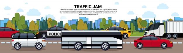 Atasco de tráfico con autos y autobuses en carretera sobre edificios de la ciudad