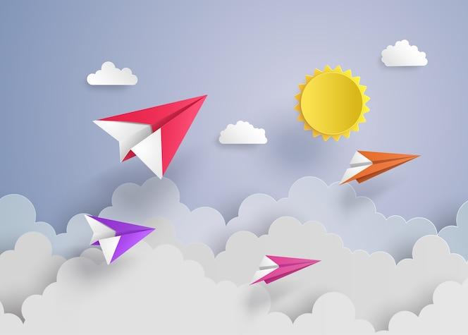 Avión de papel en el cielo azul con nubes