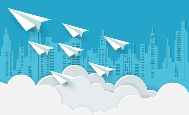 Avión de papel blanco volando en el cielo entre nubes.