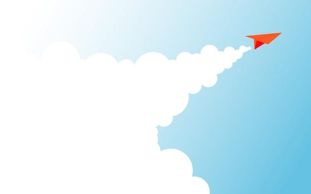 Un avión de papel naranja se eleva volando hacia el cielo a través del cielo azul claro y hace que el humo blanco del motor