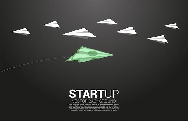El avión de papel origami de billetes de dinero va de manera diferente al grupo de blancos. concepto de negocio de inversores y capital de riesgo.