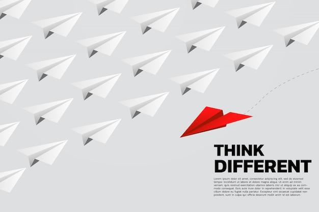 Avión de papel origami rojo va de manera diferente al grupo de blancos.