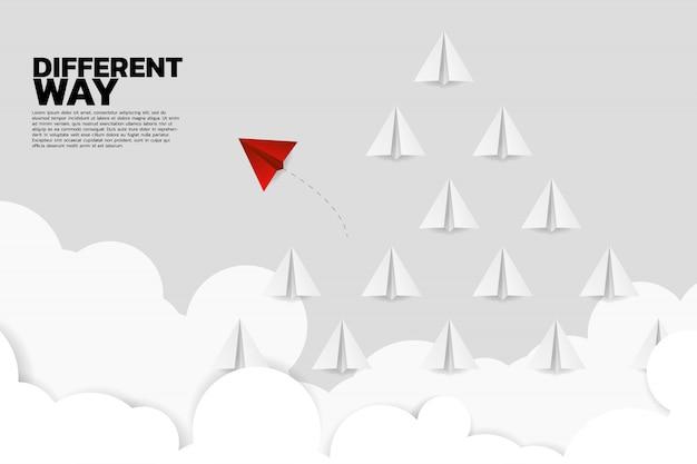 Avión de papel origami rojo va de manera diferente del grupo.