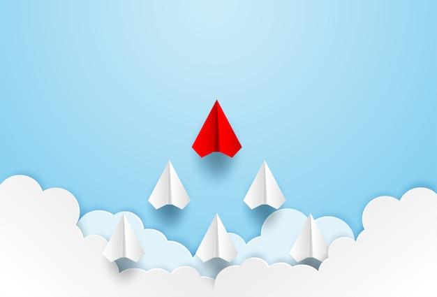 Avion de papel rojo liderando al cielo.