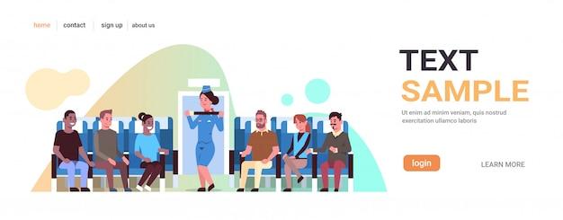Azafata explicando a los pasajeros de las carreras mixtas cómo usar el cinturón de seguridad de la azafata en el concepto de demostración de seguridad uniforme, espacio de copia horizontal del tablero del avión