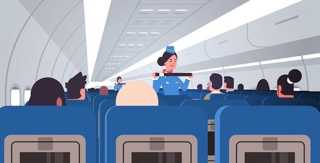 Azafata explicando a los pasajeros cómo usar el cinturón de seguridad en situaciones de emergencia, los asistentes de vuelo en concepto de demostración de seguridad uniforme tablero de avión interior horizontal