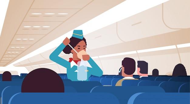 Azafata explicando a los pasajeros cómo usar la máscara de oxígeno en situaciones de emergencia asistente de vuelo afroamericano concepto de demostración de seguridad avión moderno tablero interior horizontal