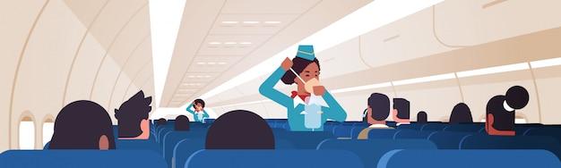 Azafata explicando a los pasajeros cómo usar la máscara de oxígeno en situaciones de emergencia asistentes de vuelo afroamericanos concepto de demostración de seguridad tablero de avión moderno interior horizontal