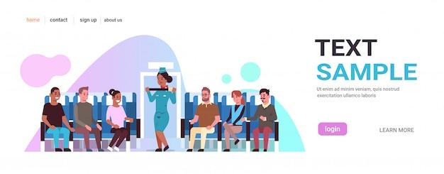 Azafata explicando a los pasajeros de la raza mixta cómo usar el cinturón de seguridad de la azafata afroamericana en un concepto de demostración de seguridad uniforme, espacio de copia horizontal en el interior del avión