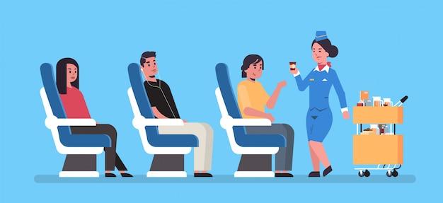 La azafata que sirve bebidas a los pasajeros de la junta del avión sentados en sillones azafata en uniforme empujando el carro de la carretilla servicio profesional concepto de viaje