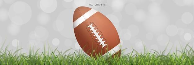 Balón de fútbol americano en el campo de hierba verde con luz de fondo bokeh borrosa