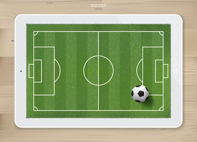 Balón de fútbol en el área del campo de fútbol en la pantalla de la tableta con fondo de textura de madera. para crear un juego de fútbol y una idea de táctica de fútbol.