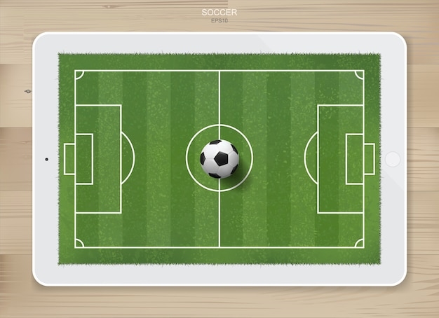 Balón de fútbol en el campo de fútbol de la pantalla de la tableta.