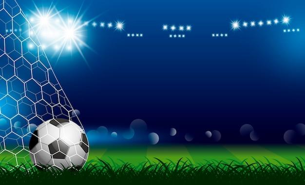 Balón de fútbol en portería sobre césped con reflector