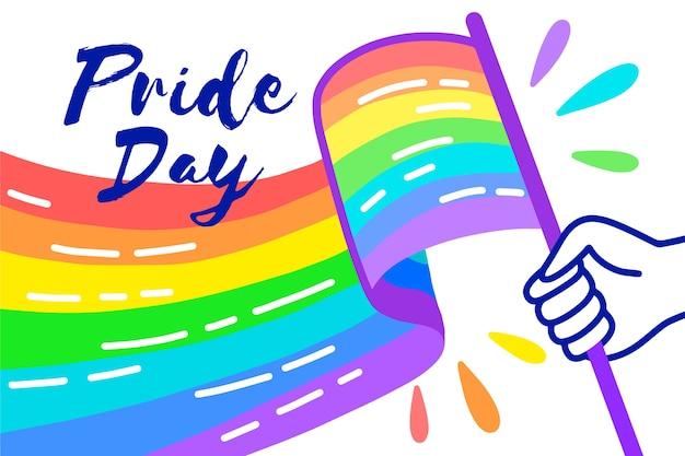 Bandera del día del orgullo arcoiris y mano