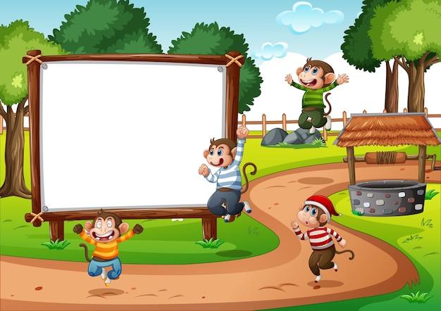 Banner en blanco de madera en la escena del parque con cuatro monos.