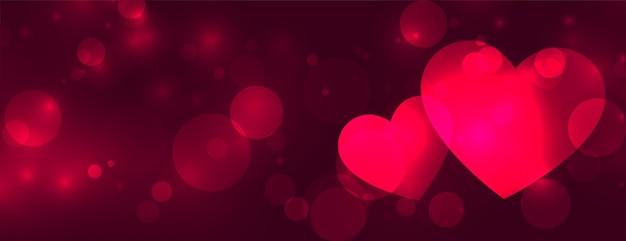 Banner de bokeh de dos corazones de amor brillante