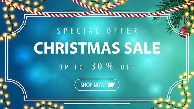 Banner de descuento horizontal azul con guirnalda y rama de árbol de navidad