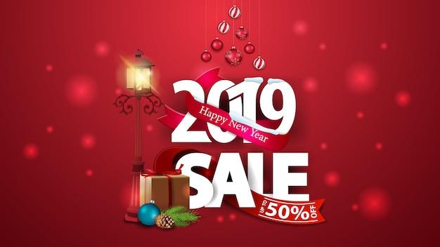 Banner de descuento rojo de año nuevo con grandes números 2019, regalos y farola antigua